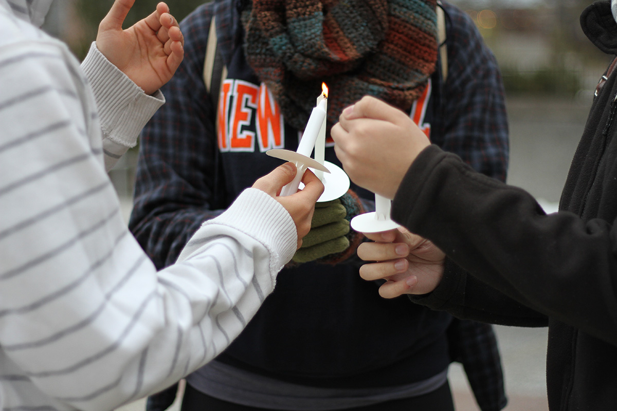 Students help each other light their candles. Photo by Gabriela Jeronimo.