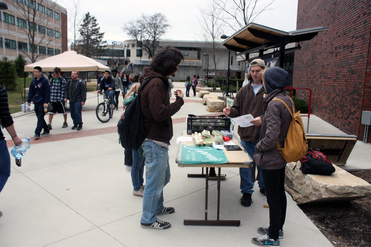 This stand is run by Students for Sustainable Agriculture, a SUNY New Paltz student group that works to promote a sustainable food system that is healthy for consumers, farmworkers, and the environment. Jacob Zyskowski, a freshmen, explains to students that the eggs being sold have been provided by Old Ford Farm. Photo by Lauren Reid.