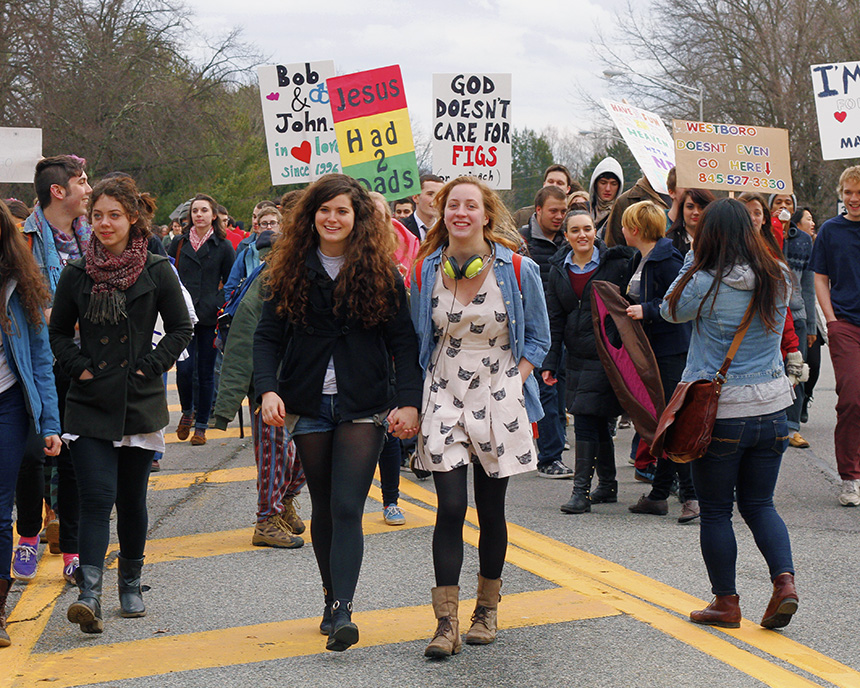 Vassar students armed with signs of their own march down the road toward the Westboro Baptist Church members. Photo by Tim Smith.