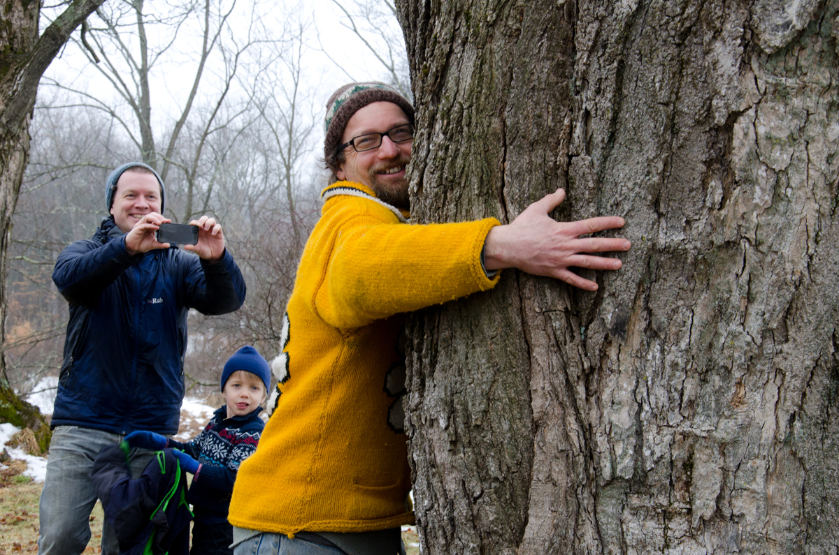 """Creek Iverson, manager of the Brook Farm Project, New Paltz NY, while giving a demonstration of tapping a sugar maple tree to a group of prep work volunteers, teaches the group that one should give the chosen sugar maple tree a hug of """"thanks"""" for sharing its sap with us so that we may enjoy maple syrup. Photo by Dawna M. Cservak."""