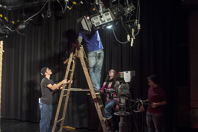 Students prepare for the first shoot of the day by adjusting the lighting and making sure the cameras are to their liking. Photo by Vincent Carnevale