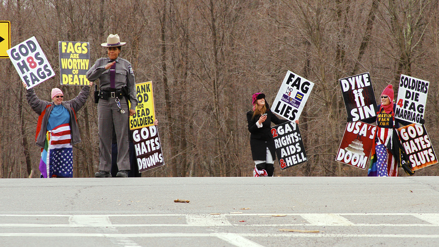 The shouts of Shirley Phelps (on right) with three other members are barely audible at the police-imposed distance from the students. The Westboro members were smiling and playing with their phones. Photo by Tim Smith.