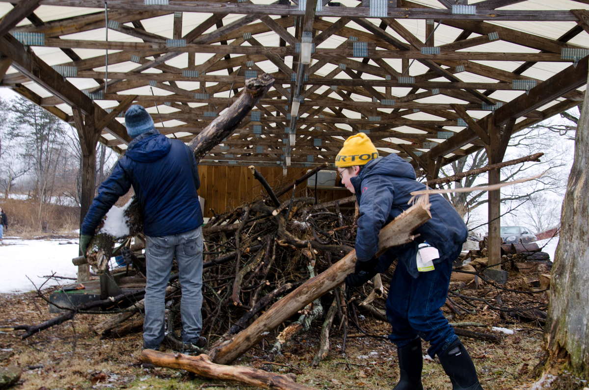 Local volunteers Stephen Gilman (left) and Seamus Schwartz help gather wood in preparation for use in building fires to boil the sap once the sugar maple trees have been tapped. Photo by Dawna M. Cservak.