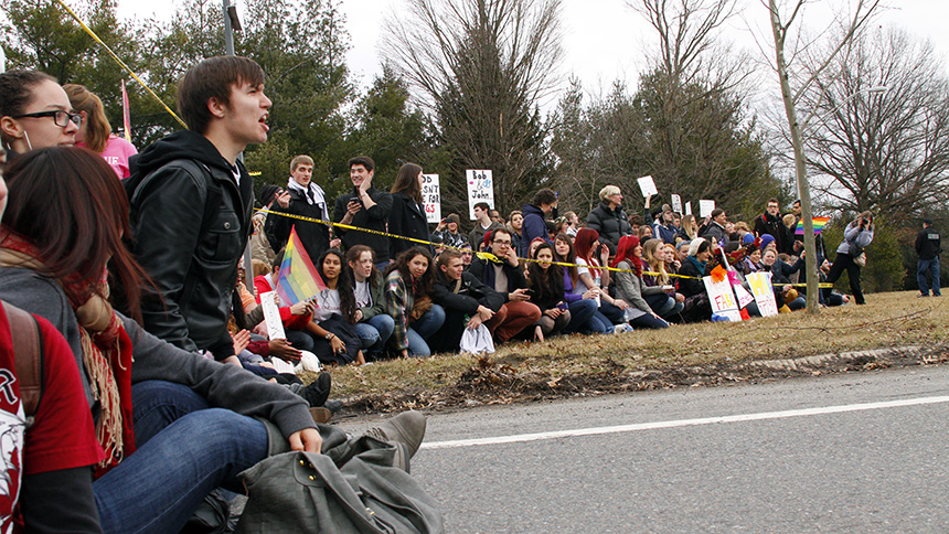 Anti-protestors at the front of the police-lined boundary sit down. The reactions of the students vary, some are angry, others stoic, while others are laughing. Photo by Tim Smith.
