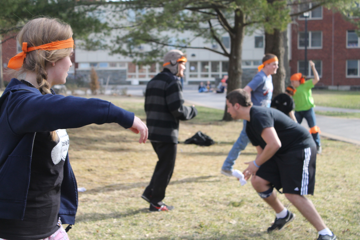 "A group of ""zombies"" are preparing for a mission by stretching and practicing their attacks before a game of Humans vs. Zombies at SUNY New Paltz. Throughout the game, moderators organize missions, or special events that cause the ""humans"" and ""zombies"" to come into close contact with each other. Missions include scavenger hunts, solving puzzles, defending points and other small games. Photo by Faith Gimzek."