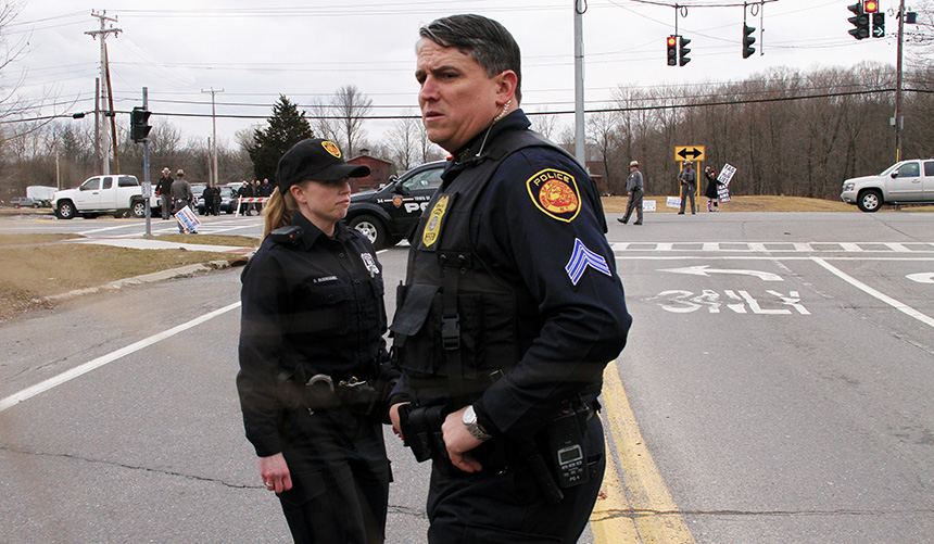 Police officers assigned to protect the Westboro members look over the mob of students. To avoid altercations students are kept far out of throwing distance from the protestors. Photo by Tim Smith.