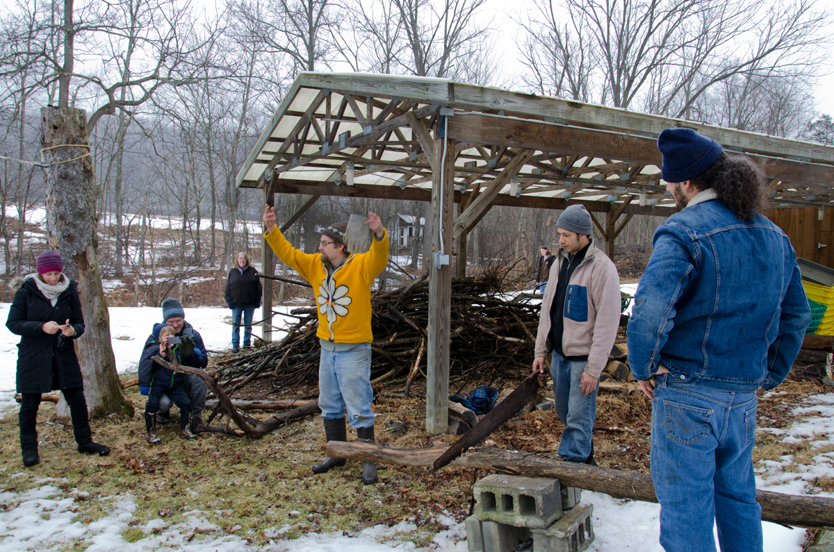 Creek Iverson, manager of the Brook Farm Project (in the center wearing the yellow sweater), passes over the saw to volunteer Zach Baker of NYC, so that he may teach the lumberjack song to the group for a sing a long. Photo by Dawna M. Cservak.