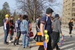 "A group of ""humans"", identified by orange armbands, prepare to defend themselves from ""zombie"" attack with foam projectile blasters in a game of Humans vs. Zombies. Photo by Faith Gimzek."