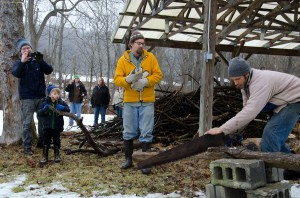 Led by Creek Iverson, manager of the Brook Farm Project (second from the right), the group of volunteers participate in a sing a long to a customary lumberjack song, while Zack Baker of NYC, cuts the wood for the fire. Photo by Dawna M. Cservak.