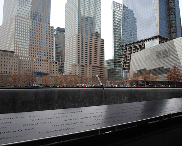 Hundreds of people gathered around the edges of the fountains reading each of the names, gazing into the water, saying prayers, consoling others, and taking pictures. It is almost silent as visitors walked around every edge not missing a single name. Looking up they can see the new World Trade Center building still in the process of completion. The September 11 Memorial attracts an average of 140,000 visitors every day, according to security officials. Photo by Emily DeFranco.