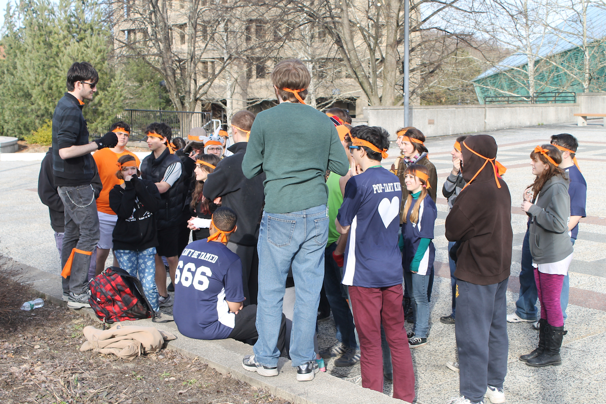 "A group of ""zombies"", identified by orange ribbons on their heads, listens to a ""human"" liaison give instructions about the day's mission in a week-long game of Humans vs. Zombies on the academic concourse at SUNY New Paltz. Photo by Faith Gimzek."