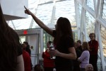 "Corrina Carraci gives the ""One Billion"" symbol to the crowd moments before the flash mob. Photo by Lauren Reid."