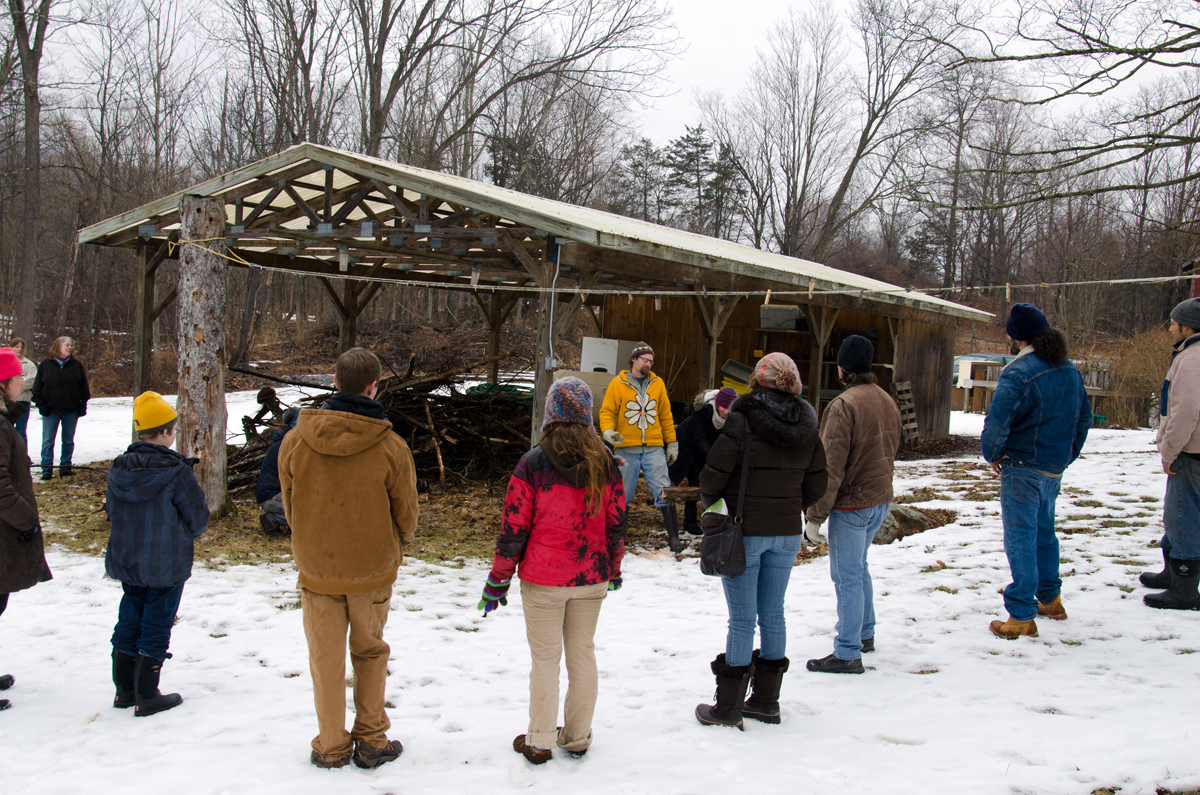 The group of volunteers at the Maple Sugaring Prep Work and Potluck, taking place at the Brook Farm project in New Paltz, NY, gather around farm manager Creek Iverson to participate in the lumberjack song sing a long. Photo by Dawna M. Cservak.