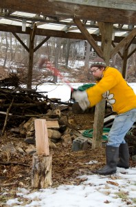 Creek Iverson, manager of the Brook Farm Project, New Paltz, NY, prepares to chop wood for the wood burner inside of the farmhouse where volunteers are taking a break to escape the drizzly damp day. Photo by Dawna M. Cservak.