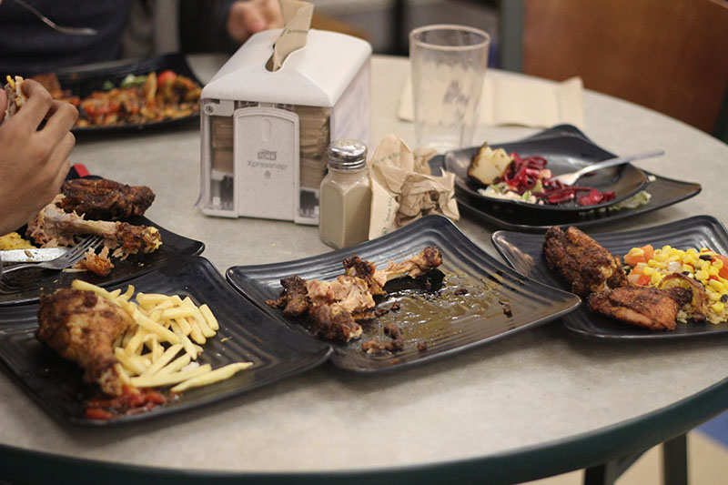 A table with plates of food on it at the all-you-can-eat Hasbrouck Dining Hall where students often take more than two full plates of food back to their tables. This photo shows students in the middle of their meal, leaving it to question how much of the food will actually be eaten, or wasted. This photo illustrates the potential for food waste, an issue that society should not ignore. Photo by Anthony Lorino.