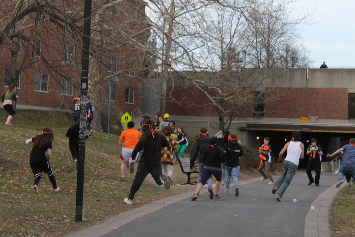 "A Humans vs. Zombies melee occurs during a mission on Pond Road behind Capen Hall at SUNY New Paltz. The ""zombies"" try to attack the ""humans"" in order to turn them into ""zombies"", while the ""humans are trying to stun the ""zombies"" with socks and foam projectiles. Photo by Faith Gimzek."