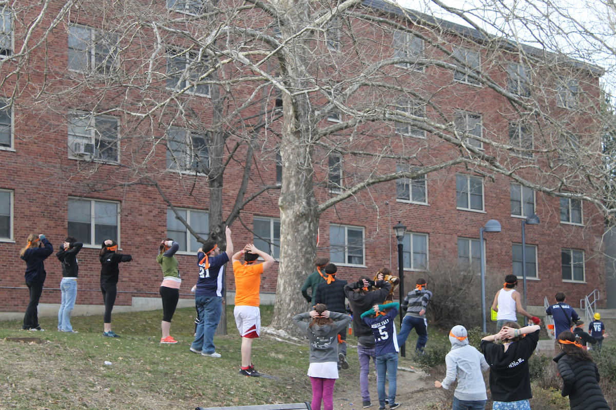 "Each ""zombie"", identified with an orange ribbon on their head, shows that they are stunned by placing their hands on their heads after a melee on Pond Road on campus, giving the ""humans"" time to escape. Photo by Faith Gimzek."