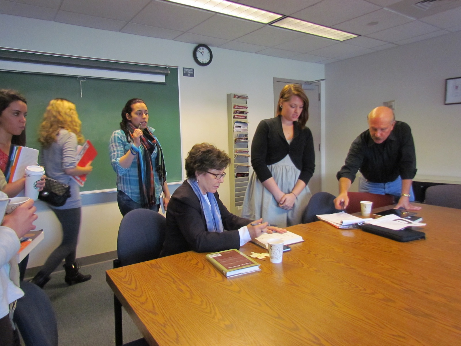 In Robert Miraldi's Journalism 1 class Amos signs copies of her book Eclipse of the Sunnis. Photo by Smaranda Dumitru.