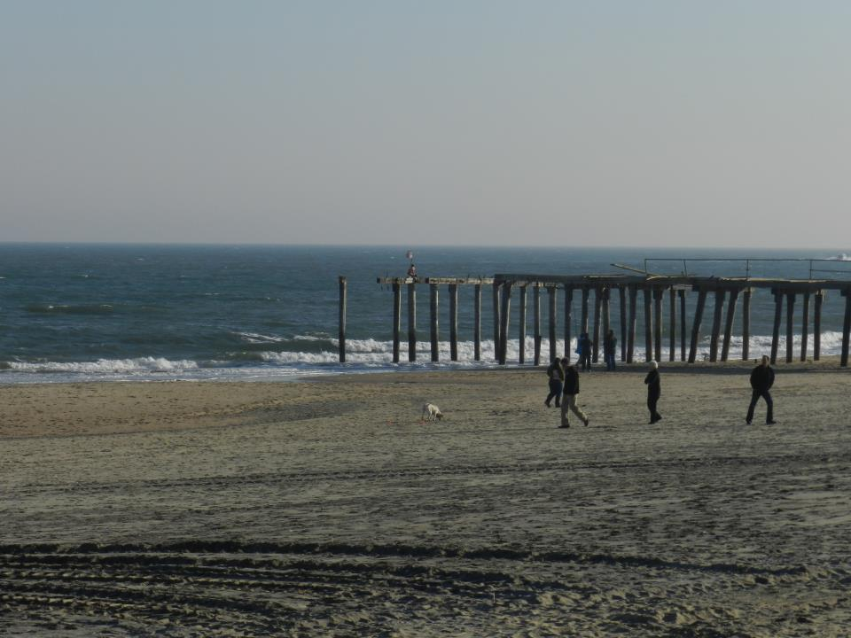 People walk on the Ocean Grove beach beneath what used to be a fishing pier. Photo by Natalie De Gaetano.