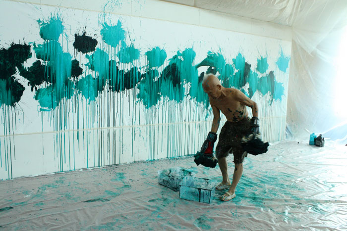 Ushio dips his gloves again. Ushio Shinohara doing his signature boxing painting. Photo by Ethan Genter