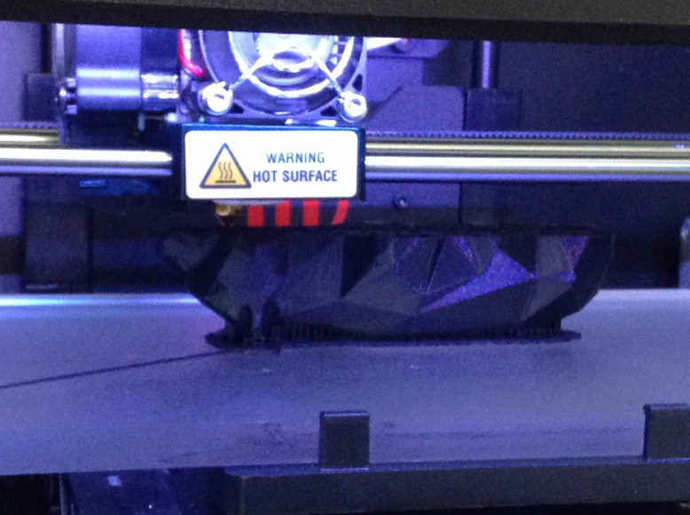 A Makerbot printer is in the process of printing out a sculpture bear