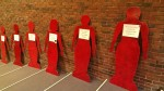 At least 15 human-sized cardboard cutouts, spray painted red, lined a wall of the room. Attached to each cutout was a sheet of paper that listed a woman's name, the date of her murder, and what town or county it occurred in. Photo by Hannah Nesich.