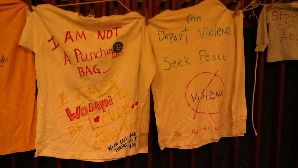 T-shirts with inspirational phrases written on them in colored marker hung from the back wall. Photo by Hannah Nesich.