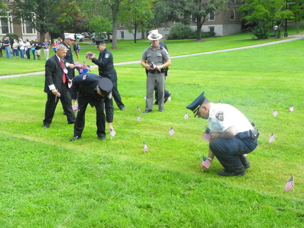 Police planting American flags during Friday's ceremony. Photo by Justin Sarjeant.