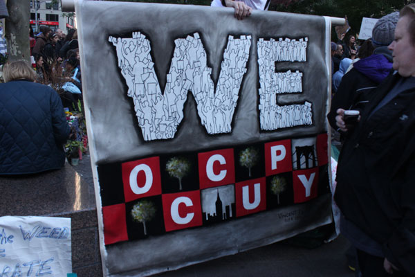 "A canvas reads ""We Occupy"" at the Occupy Wall Street protests at Zucotti Park. Photo by Kathy Kim"