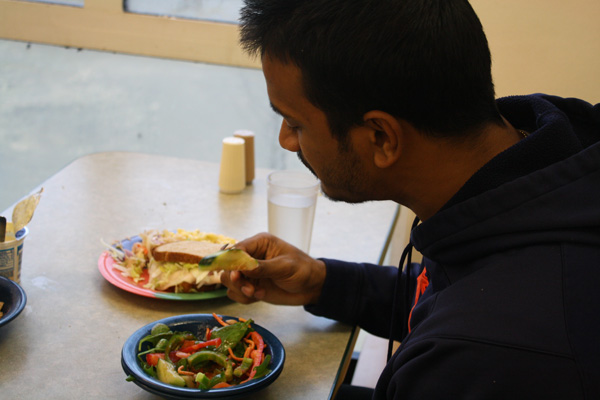 Arun Mathew, a second-year finance and mathematics major, enjoys a light salad with a friend in Hasbrouck Dining Hall. Photo by Courtney Moore.