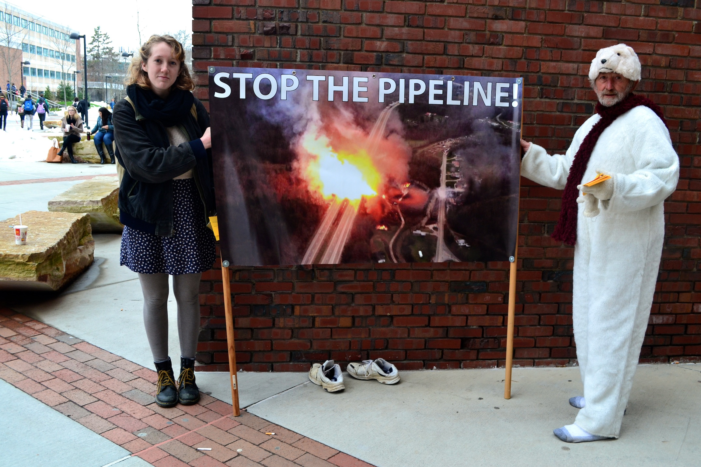 Anna Budinger, environmental indigenous studies major stands beside Joe Barbarito, a Climate Action Coalition member promote the demonstration on campus a day prior.