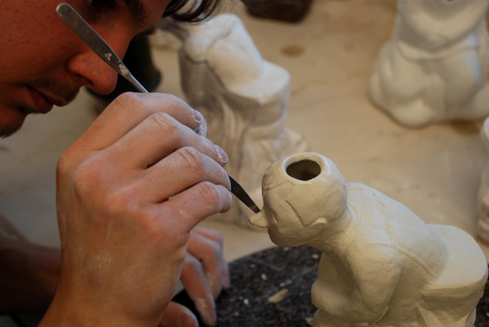 Ceramic student Kyle Gredder touches up one of his many buddha-like molds. Photo by Lindsay Cooper.
