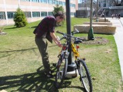 Third-year digital media production major Jared Loperfido locks up his bike outside the Coykendale Science Building before a Milestones in Documentary class. He rides his bike to class from his off-campus apartment about five minutes away. Many students at SUNY New Paltz use bikes as a fast, cheap and eco-friendly way to get around campus and around town. Photo by Faith Gimzek.