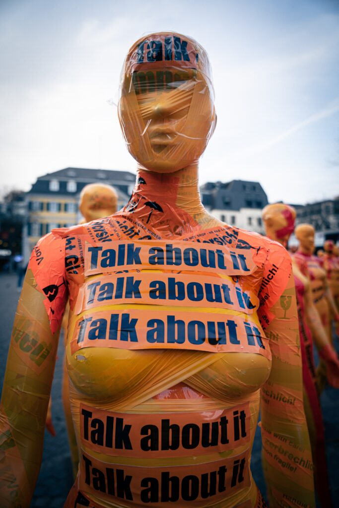 """Mannequin with """"talk about it"""" tape wrapping body"""