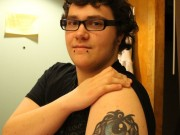 Adams shows off his first tattoo, which symbolizes his transition. The tribal pattern on the top is a replica of the design on a ring his grandmother gave him when he first told her about wanting to change his gender identity. The round shape on the left side of the eye represents being female, while the diamond shape on the right side represents being male. Photo by Faith Gimzek.