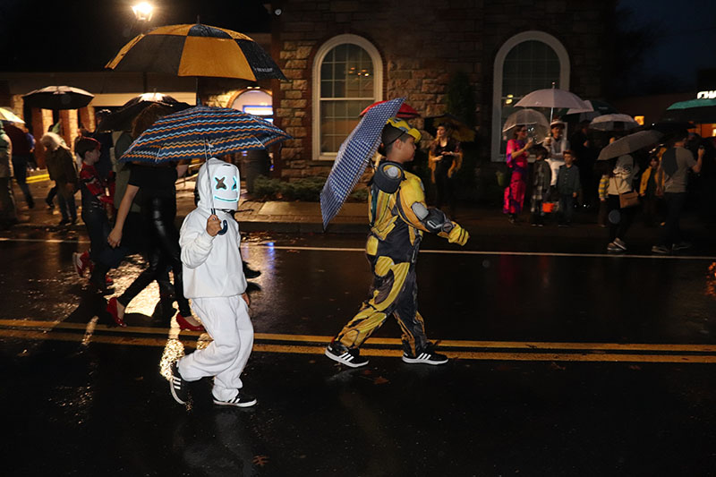 Two kids walk in the parade while shielding themselves from the rainy weather.